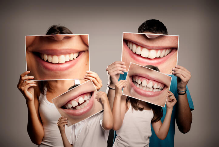 oral hygiene - a family holding photos of their smiles at beach grove dental tsawwassen